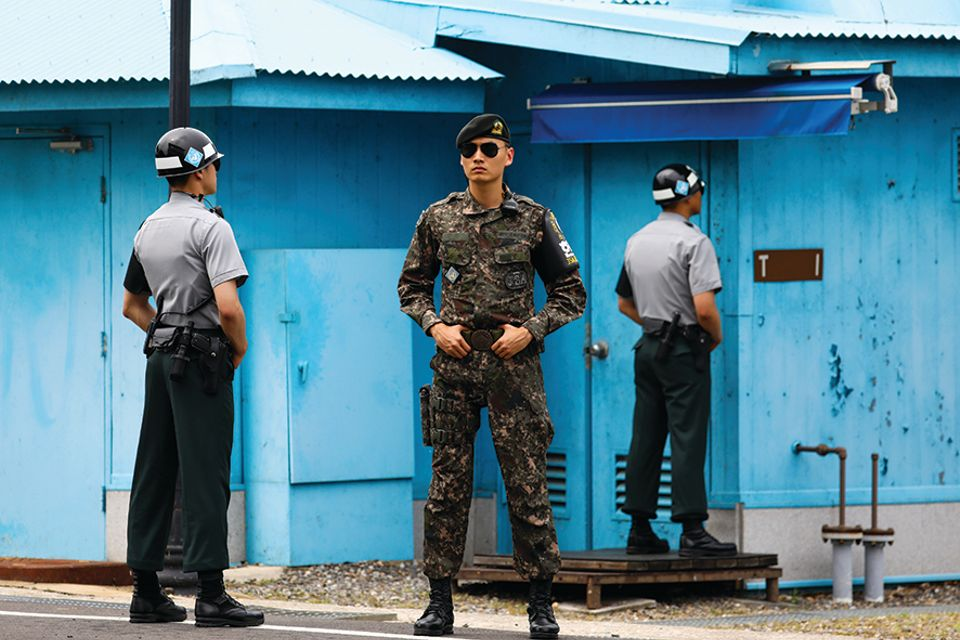 South Korean soldiers stand guard in the Demilitarized Zone (DMZ), which the Scottish artist Douglas Gordon has tattooed on a refugee's back