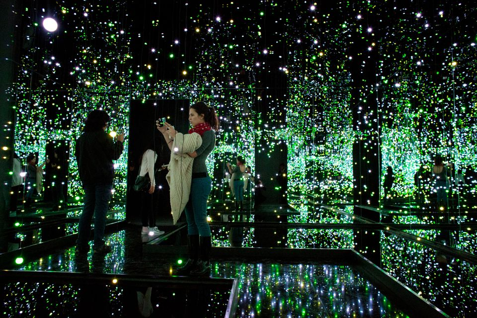Journalists take pictures of an installation by Japanese artist Yayoi Kusama during a press tour of her