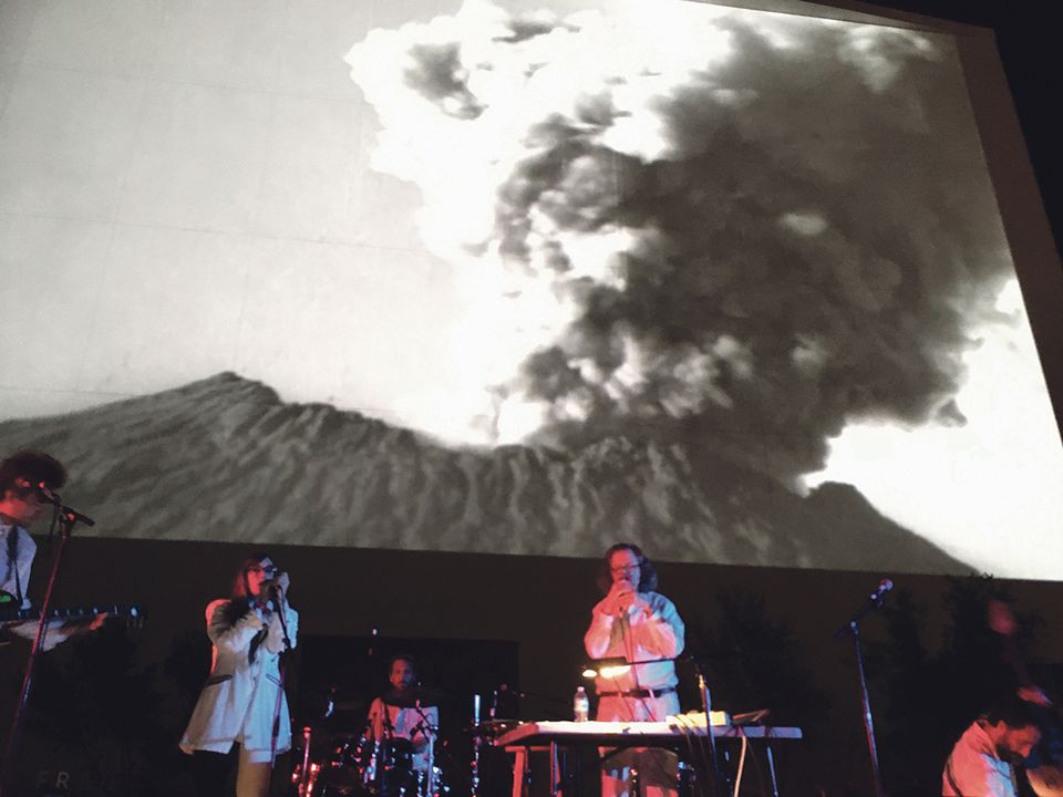 Jim Shaw and his band perform against the background of an erupting volcano