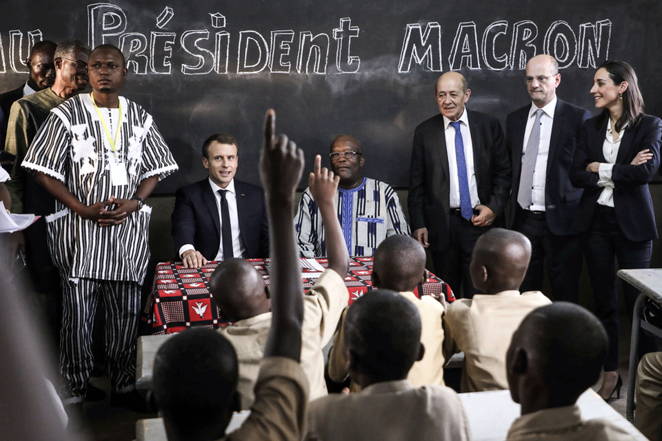 French President Emmanuel Macron and Burkina Faso's President Roch Marc Christian Kabore sit in a classroom as they visit the Lagm Taaba school in Ouagadougou, as part of his first African tour since taking office