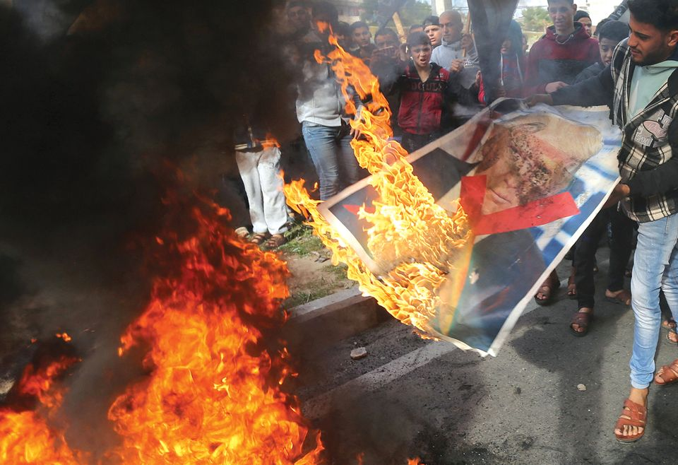Protesters near the Gaza Strip burn an effigy of Donald Trump