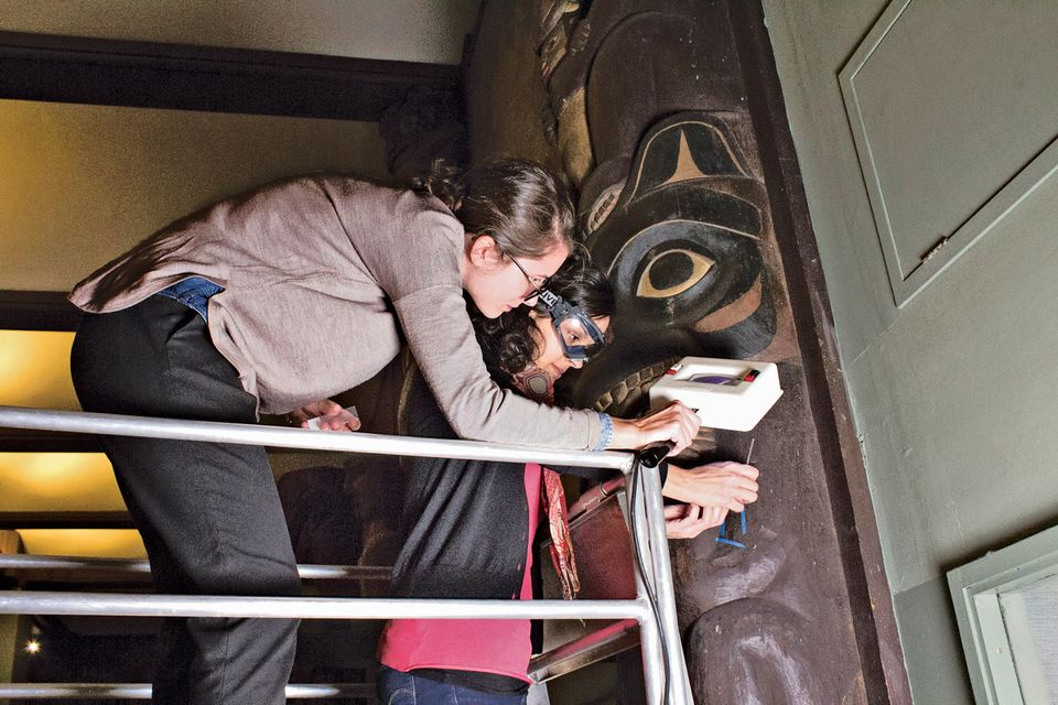 Federica Pozzi and Anna Cesaratto remove samples from a Tsimshian house post