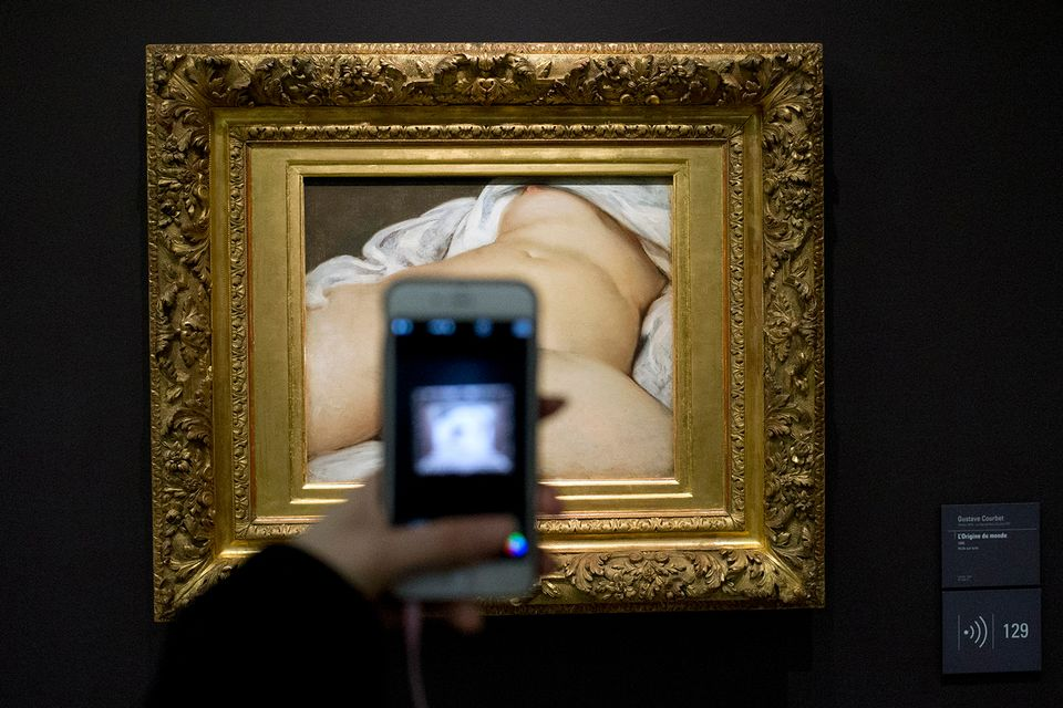 A visitor takes a picture of Gustave Courbet's 1866 The Origin of the World, at Musee d'Orsay museum, in Paris. A French teacher, whose Facebook account was suspended in 2011 after he posted a photo of a famous 19th-century nude painting, is suing Thursday Feb. 1, 2018 the California-based social network Facebook for alleged censorship. Frederic Durand-Baissas, a 59-year-old Parisian teacher and art lover, posted a photo of The Origin of the World, which depicts female genitalia. ()