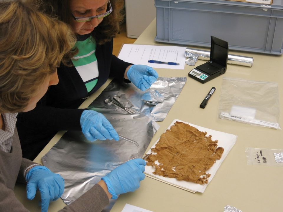 Conservators placed the brittle papyrus  in a humid chamber to restore its flexibility before it was treated with cellulose and smoothed with a suction table and weights