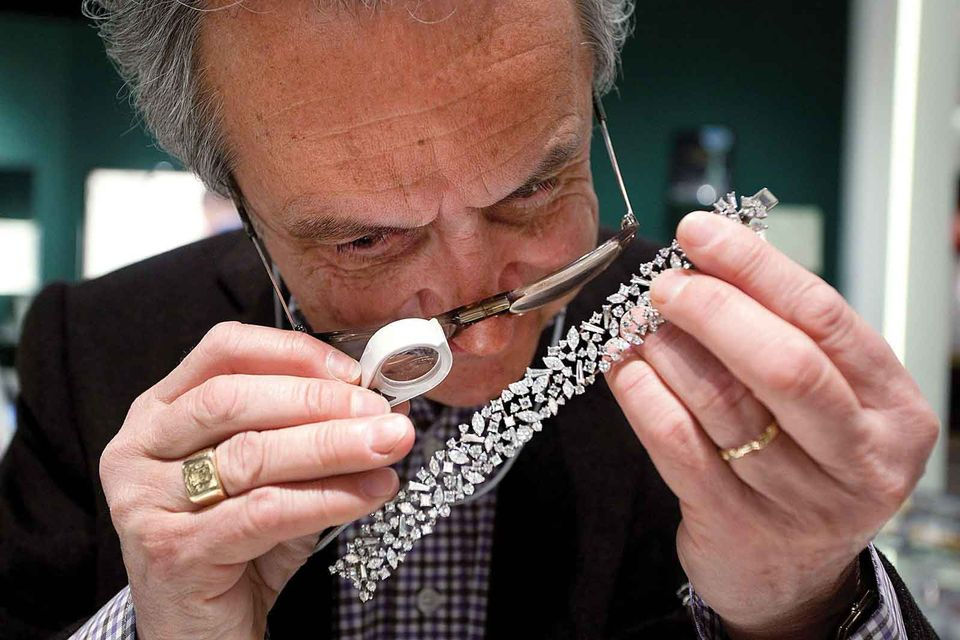 An expert examining a piece of jewellery