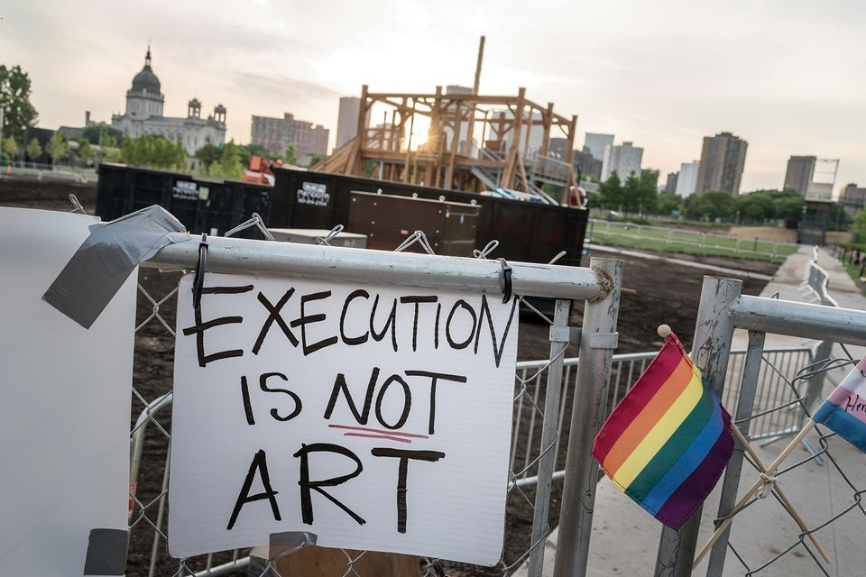 A protest sign hangs on a fence surround Sam Durant's Scaffold sculpture at the Walker Art Center's sculpture garden