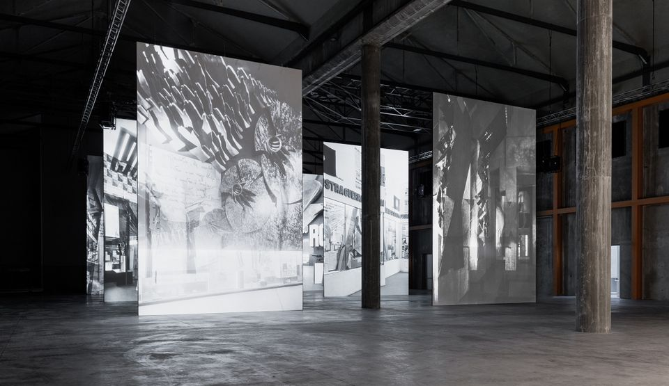 Archival photographs of the 1932 Mostra della Rivoluzione Fascista are projected on to huge screens in the Prada foundation's massive Deposito space