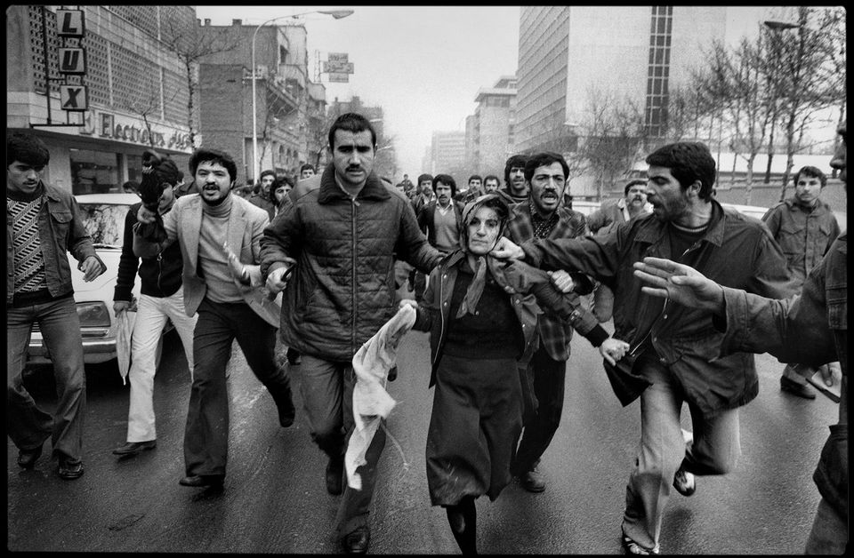 After a demonstration at the Amjadiyeh Stadium in Tehran, Iran, 25 January 1979, in support of the Constitution and of Shapour Bakhtiar, who was appointed Prime Minister by the Shah before he left the country, a woman, believed to be a supporter of the Shah is mobbed by a revolutionary crowd