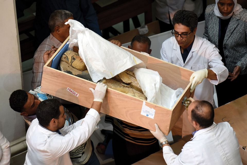 Egyptian museum staff with a sarcophagus repatriated by the Israeli government in 2016 after discovering it had been looted