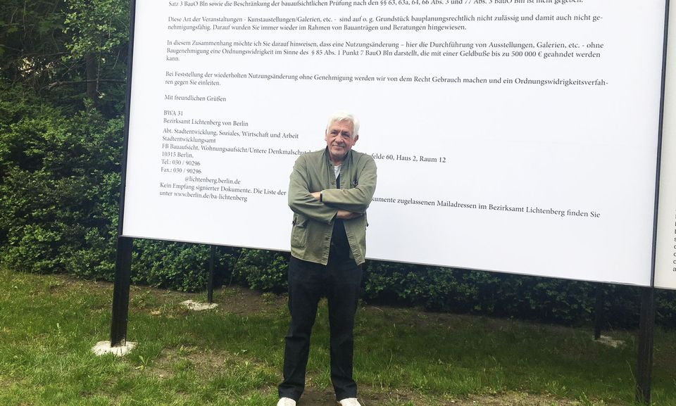 The collector Axel Haubrok in front of a giant copy of the email he received from the local authority saying his exhibition space is violating zoning laws