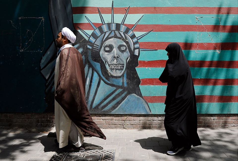 Mandatory Credit: Photo by  (9673547m) An Iranian cleric and a woman walk past an anti-US moral  during an anti-US and Israeli protest outside the former US embassy in Tehran, Iran, 16 May 2018.  Iranian held a protest to shows their support for the protests in Gaza and the West Bank against the transfer of the US embassy from Tel Aviv to Jerusalem. At least 62 Palestinian protesters were killed and more than 2,500 others were injured at the Gaza-Israeli border during clashes against the US embassy move to Jerusalem as well as marking the Nakba Day. Protest in solidarity with Gaza in Tehran, Iran (Islamic Republic Of) - 16 May 2018