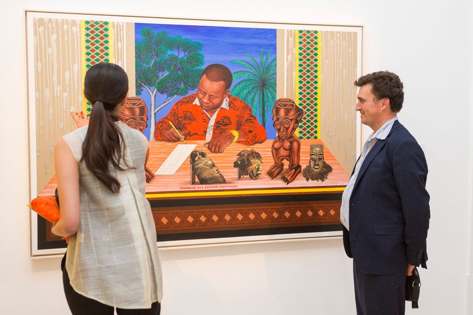 Visitors view one of Cheri Samba's paintings in African Passions