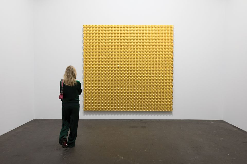 """It's like an egg carton blown up to an incredible size. Because it is a square and a wall piece, it has a certain relationship to painting although it is clearly not a hand-painted canvas. The gold leaf offers a second reference to religious paintings, as it was often used to show the importance of saints. The single egg [in the work] is an autobiographical element because the artist was an only child so his socialisation and his becoming who he is today was influenced by Chinese policy, which meant that boys and girls of his generation are only children. On the wall are family photographs; one shows him as a child standing in Tiananmen Square eight years after the [1989] massacre. I asked him if he knew about it when he posed for the picture and he said that he only found out about it in college. It shows us a certain innocence and the loneliness of being an only child and how it can have an impact on a society and on a life."""