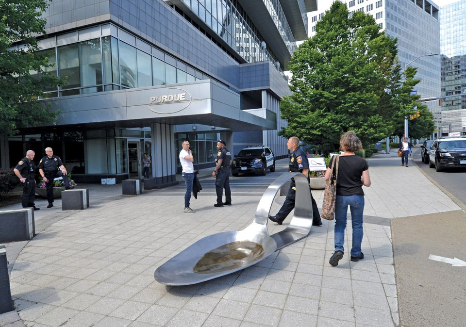 Domenic Esposito's opium-spoon sculpture was placed outside Purdue Pharma's offices by the gallery owner Fernando Luis Alvarez (in white shirt), who was later arrested for refusing to remove it