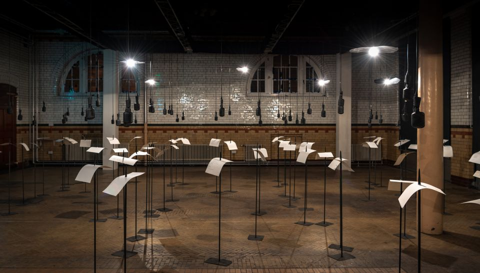 "A forest of 100 microphones and 100 impaled papers fills the Edinburgh College of Art's Engine House. The microphones, suspended above fragments of poetry on the spears below, recite the words of poets who have been censored and silenced over the last century. For, in your tongue I cannot hide (2018) (until 26 August) by the Indian artist Shilpa Gupta refers to the continued vulnerability of freedom of expression today. Lasting over an hour, each microphone plays its verse and alternates between languages including English, Spanish, Arabic, Russian, Azeri and Hindi. The work, which is co-commissioned with YARAT Contemporary Art Space in Baku, is one of five commissions in the EAF programme this year, focussing on performance-based works that ""reflect on urgent current political issues""."