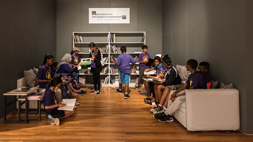 Children look through art books in another part of the exhibition at the Aga Khan Museum
