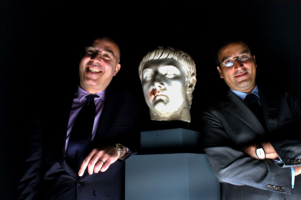 Ali Aboutaam, left, and brother Hicham Aboutaam of the Phoenix Ancient Art Company pose with a monumental marble head of the Emperor Tiberius, which is not believed to be among the seized items