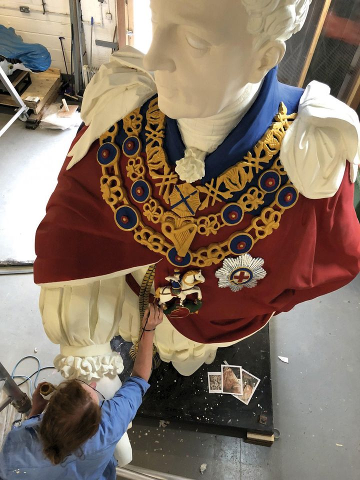 "A conservator works on ""King Billy"", the figurehead of the 1830s HMS Royal William"