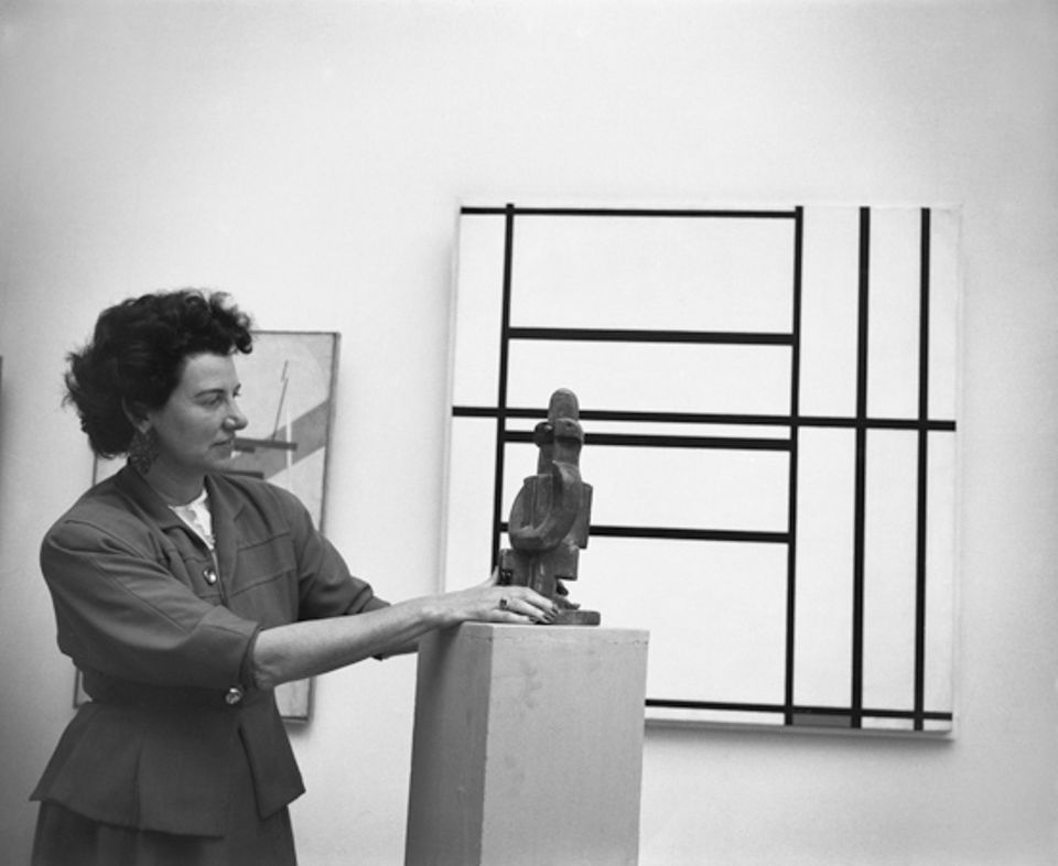 Peggy Guggenheim at the Greek Pavilion, where she exhibited her collection at the 24th Venice Biennale in 1948, next to Jacques Lipchitz, Seated Pierrot (1922); in the background Piet Mondrian, Composition No. 1 with Grey and Red 1938 / Composition with Red 1939 (1938-39)