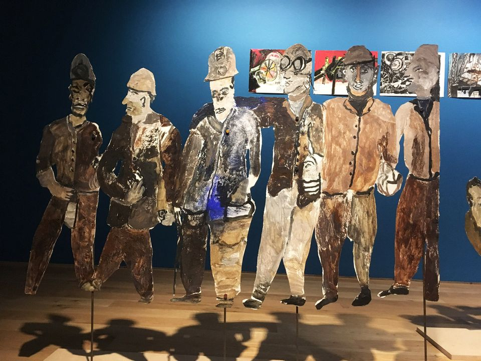 "As well as the steel silhouettes, Boghiguian's installation includes her signature paper cut-outs with rows of dirtied workers in hard hats. One of her scenes shows workers during down time, reading or playing cards, while another shows them protesting with one placard demanding ""better pension plans""."
