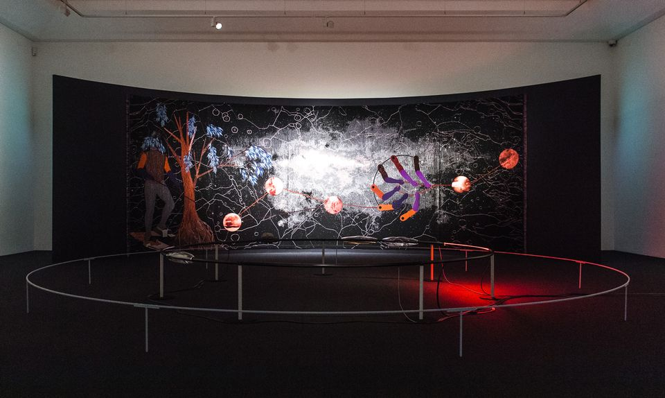 "The Nigerian artist Otobong Nkanga is showing two new works, a tapestry titled Double Plot (2018) and a sculptural work titled Manifest of Strains (2018). The latter contains several components that act on a large circular rail: one section glows red hot, another has a rock that is hovering thanks to electromagnets, while other sections are enveloped in different corrosive liquids. Nkanga has made sure that not all the elements are revealed at once. ""You're meant to look for it,"" she says."