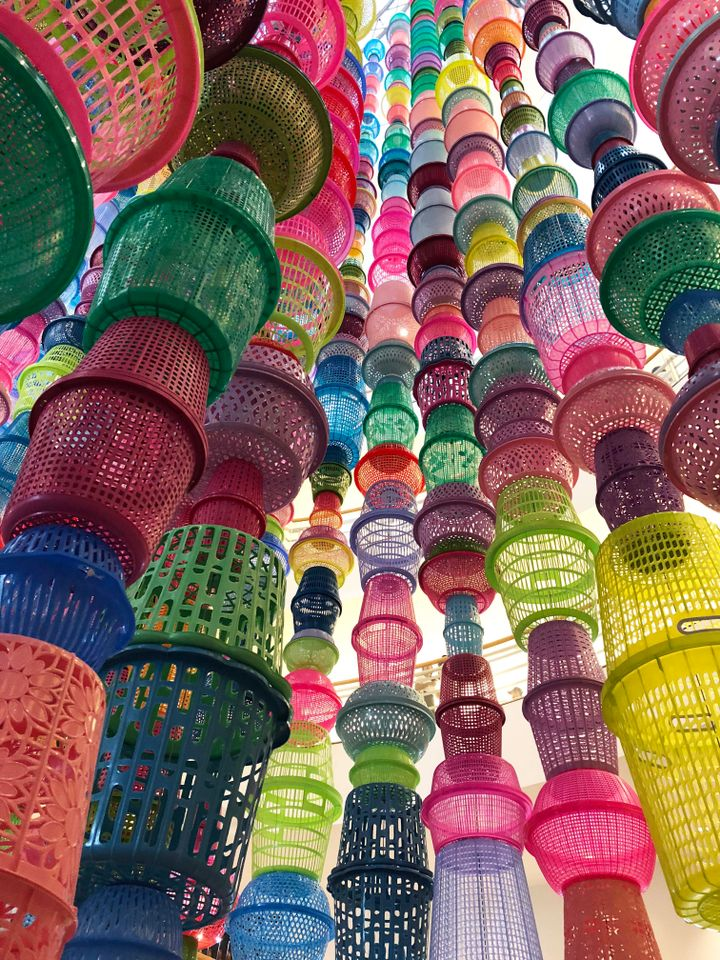 "Choi Jeong Hwa (South Korea), Tower Baskets, 2018, a soaring sculpture of brightly coloured plastic baskets, welcomes visitors to the Bangkok Art and Culture Center (BACC), one of the biennale's main sites. The work is a comment on the ""superficial happiness we live in,"" the curators say in the biennale catalogue."