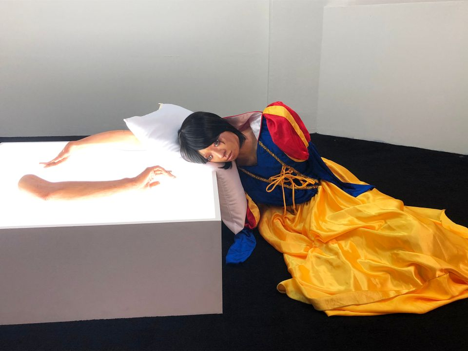 "Elsa Jocson (Phillippines) Becoming White, 2018 is a wry deconstruction of the Snow White fairy tale on display at the O.P. Place shopping mall. It consists of performance, works on paper, videos, sound installation and sculptures which critique the idea that whiteness is seen as a prerequisite for happiness. It was made in reference to Disneyland Hong Kong where ""a legion of dancers from the Philippines are employed as professional entertainers to repeat performances of happiness as their daily labour. Excluded from the main roles that are reserved for specific racial profiles, they are assigned anonymous supporting roles such as a zebra in The Lion King…[or] a monkey in Tarzan,"" the artist says in a statement in the biennale catalogue."