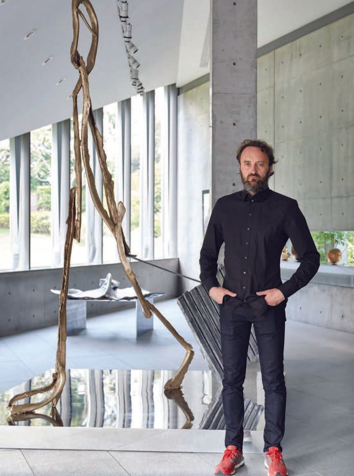 Patrick Roger with his bronze and aluminium sculpture L'homme qui voyage (The man who travels), 2017