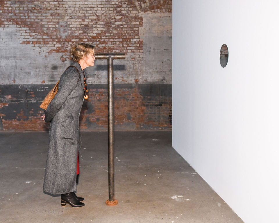 The actress Lauren Hutton peers through one of Nancy Holt's telescopes at Dia:Chelsea