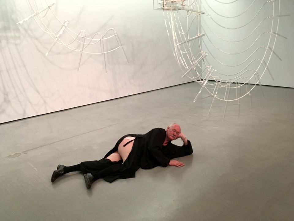 Cerith Wyn Evans reclines next to his prizewinning sculpture