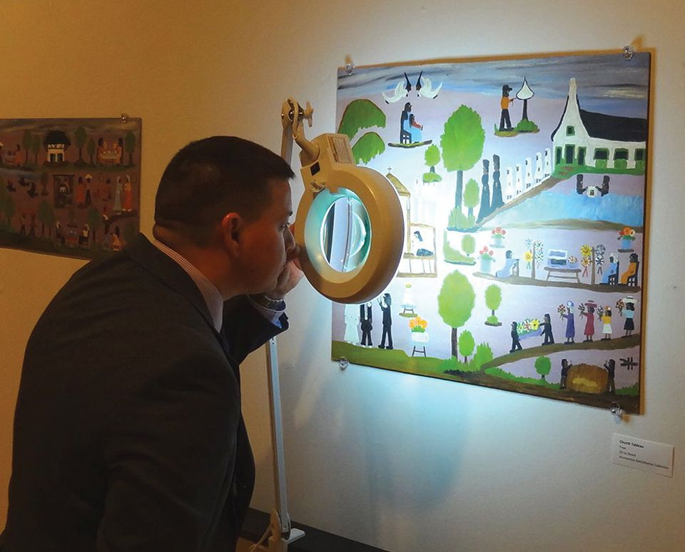 """Special Agent Randolph J. """"Randy"""" Deaton IV (Federal Bureau of Investigation) takes a close look at a Toye forgery of artist Clementine Hunter at the Gallery 2 show"""