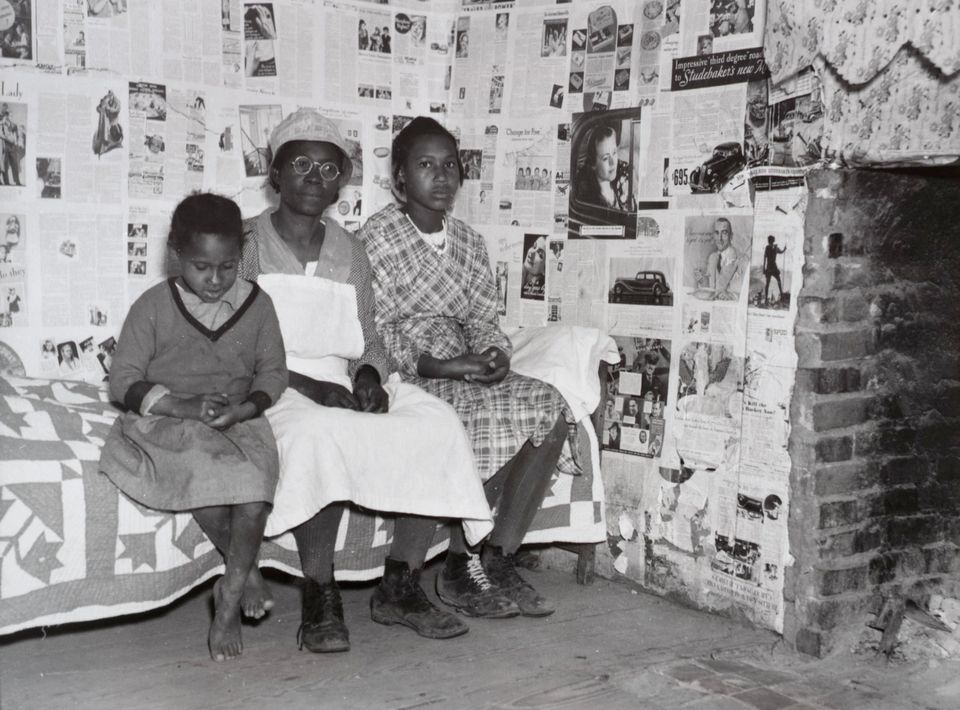Lucy Mooney and granddaughters Lucy P. Pettway and Bertha Pettway on a bed in Lucy's house, Gee's Bend, Alabama, 1937