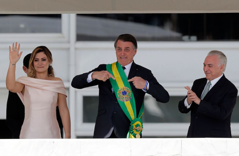 Brazil's new President Jair Bolsonaro pointing at himself after receiving the presidential sash on 1 January