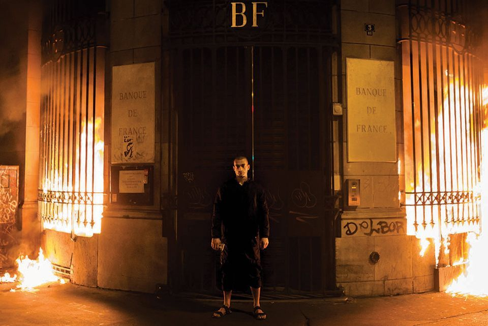 Pyotr Pavlensky poses in front of a Bank of France building after setting fire to the window gates as part of a performance in Paris
