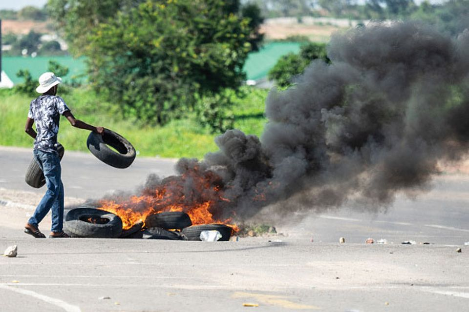 A protesters burns tyres in Bulawayo during a demonstration against the doubling of fuel prices after Zimbabwe's president announced a more than 100% rise in the price of petrol and diesel.